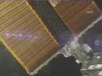 2人の宇宙飛行士が太陽電池パネルを揺らしているところ